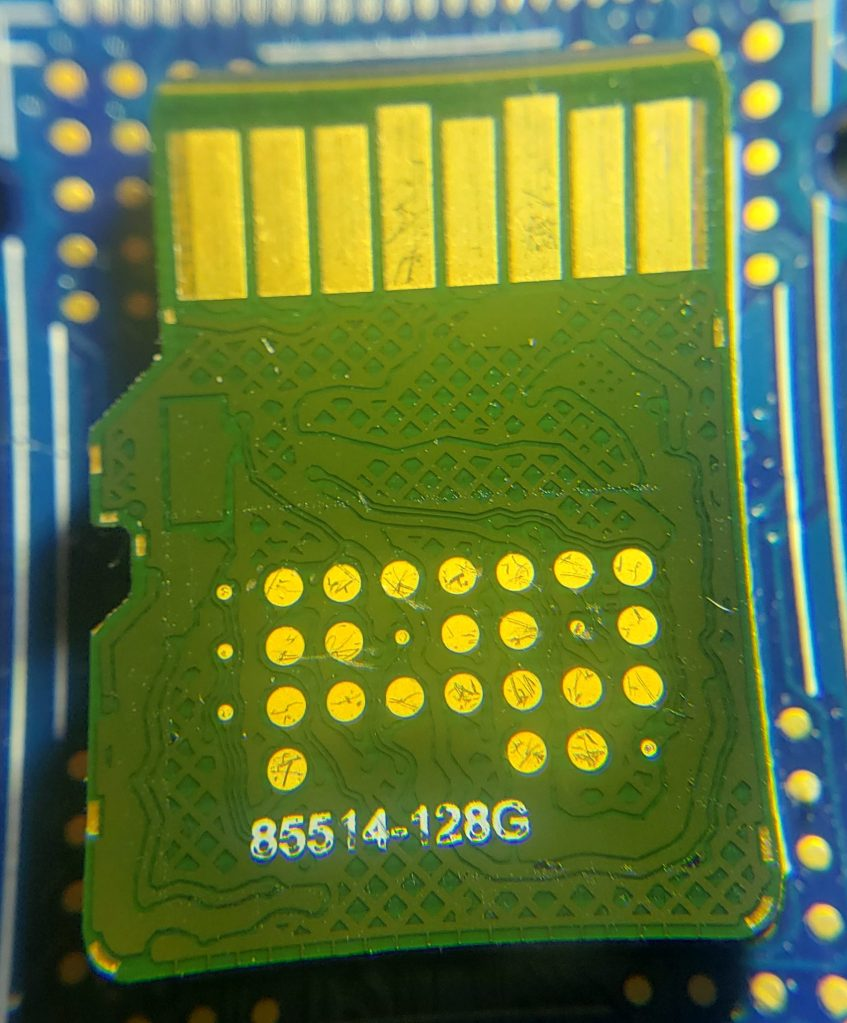 Test pads exposed on SanDisk High Endurance 128GB microSDXC card.